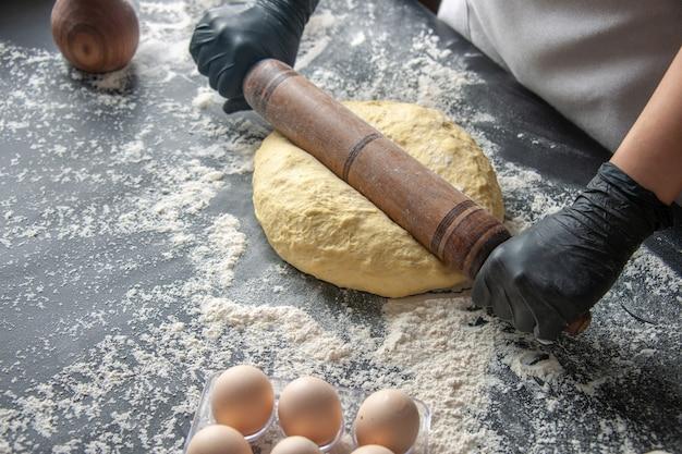 Vorderansicht köchin rollt teig mit nudelholz auf der dunklen teig-ei-job-bäckerei hotcake konditorei küche aus