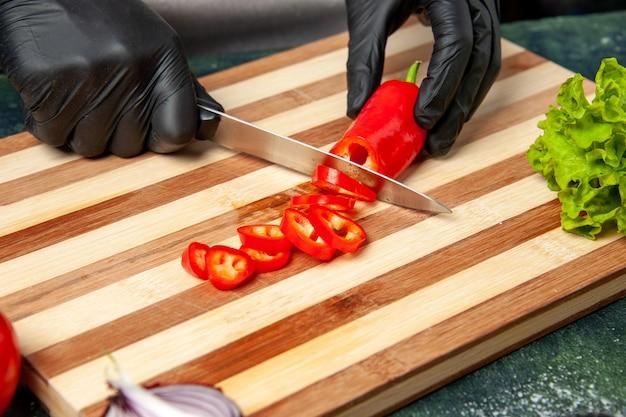 Vorderansicht köchin schneiden rote paprika auf graue lebensmittelfarbe salat küche küche mahlzeit gewürz