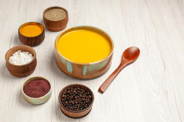 Vorderansicht köstliche cremesuppe mit verschiedenen gewürzen auf weißem holztisch suppensauce mahlzeit creme abendessen gericht