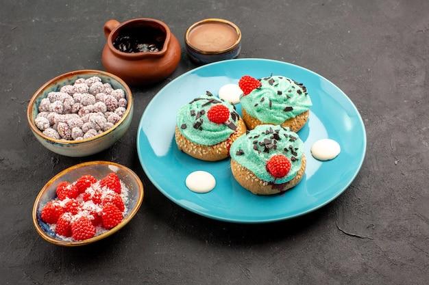 Vorderansicht köstliche cremige kuchen mit süßigkeiten auf dunklem hintergrund dessertkuchen keks süßigkeiten keksfarbe
