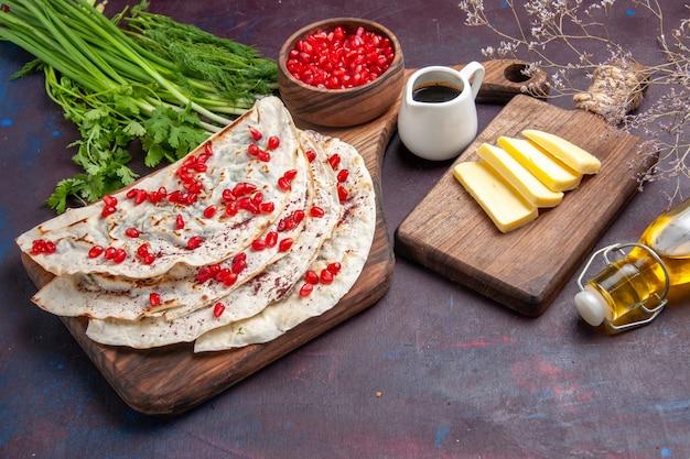 Vorderansicht köstliche fleisch-qutabs-pitas mit frischen granatäpfeln auf dunklem teig-pita-fleischmehl