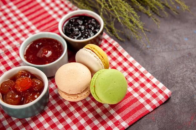 Vorderansicht köstliche französische macarons mit fruchtmarmeladen auf dunklem fruchtmarmeladenkuchenkeks süßer zucker der dunklen oberfläche