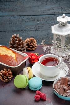 Vorderansicht köstliche französische macarons mit schokolade und tasse tee auf dunklem hintergrund kuchenkeks süßer teekuchenplätzchen