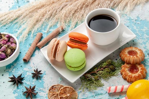 Vorderansicht köstliche französische macarons mit tasse tee und keksen auf blauer oberfläche