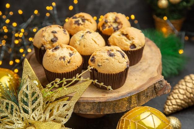 Vorderansicht köstliche fruchtige kuchen um feiertagsbaumspielzeug auf dunklem hintergrund dessertkuchen süßigkeiten fotocreme