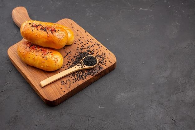 Vorderansicht köstliche gebackene pastetchen frisch aus dem ofen auf dem dunklen hintergrund kuchengebäck backen teig ofen fleischkuchen