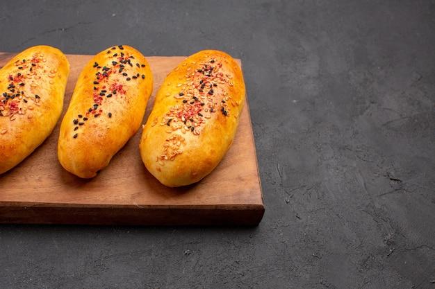Vorderansicht köstliche gebackene pastetchen frisch aus dem ofen auf dunkelgrauem hintergrundkuchengebäck-teigofen-fleischkuchen backen