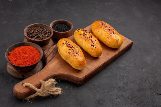 Vorderansicht köstliche gebackene pastetchen frisch aus dem ofen mit gewürzen auf grauem hintergrund kuchenofen gebäck fleisch kuchen backen