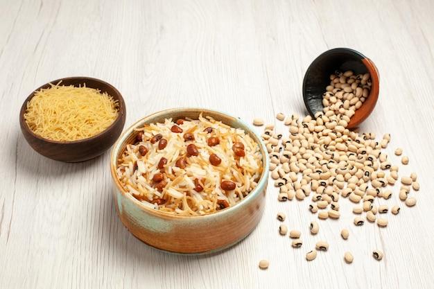Vorderansicht köstliche gekochte fadennudeln mit bohnen auf einem hellweißen schreibtischbohnenmehl, das nudelgerichte kocht
