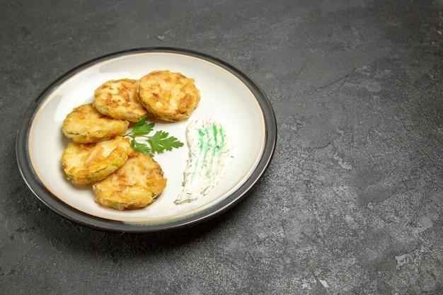 Vorderansicht köstliche gekochte kürbisscheiben innerhalb platte auf einem dunkelgrauen raum