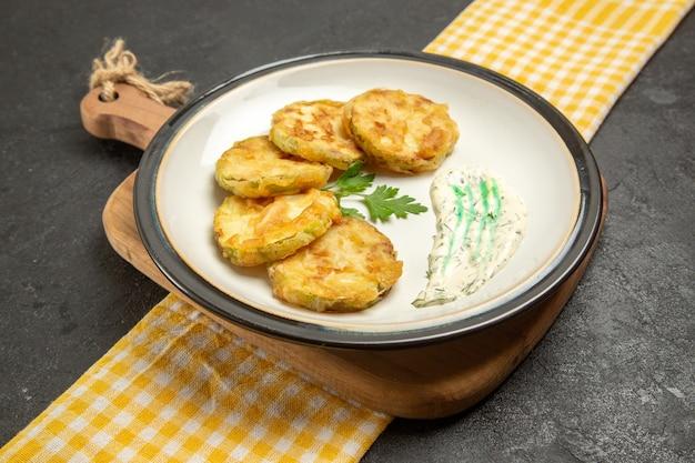 Vorderansicht köstliche gekochte kürbisscheiben innerhalb platte auf grauem raum