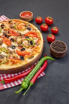 Vorderansicht köstliche käsepizza besteht aus oliven pfeffer und tomaten auf dunkler oberfläche