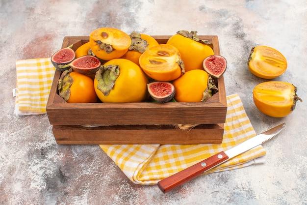 Vorderansicht köstliche kaki und geschnittene feigen in holzkiste gelbes küchentuch ein messer auf nacktem hintergrund