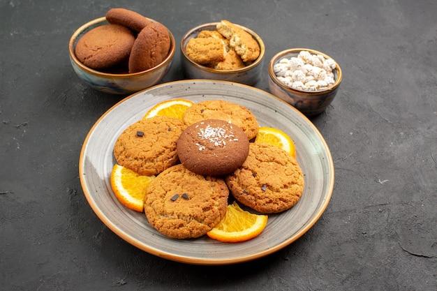 Vorderansicht köstliche kekse mit frisch geschnittenen orangen auf dunklem hintergrund obstkekskuchen zitruskeks süß