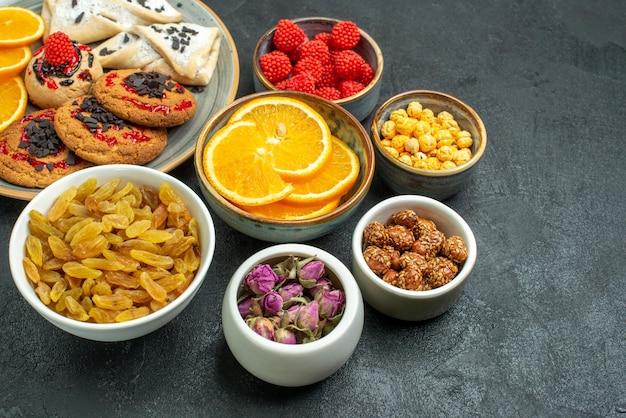 Vorderansicht köstliche kekse mit rosinen orange und konfitüren auf dunkler oberfläche fruchtsüßigkeit süßer kuchentee