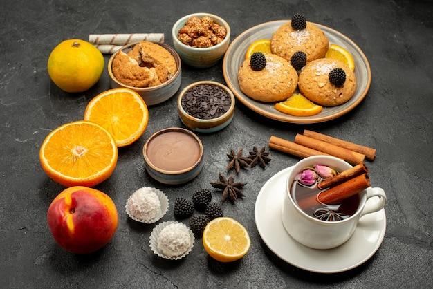 Vorderansicht köstliche kekse mit tasse tee und orangenscheiben auf dunklem hintergrund teetorte keks kekskuchen