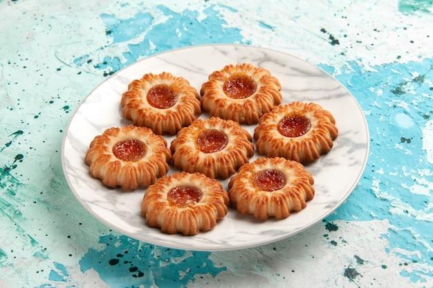 Vorderansicht köstliche kekse rund geformt mit marmelade innenplatte auf hellblauem wandkekszucker süßer keksteigkuchen backen