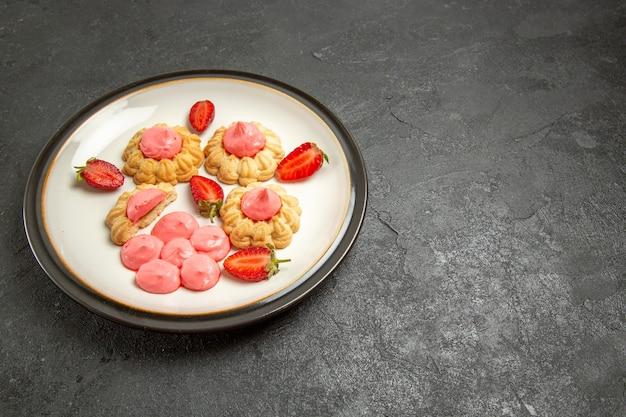 Vorderansicht köstliche kleine kekse mit rosa creme innenplatte auf grauzone