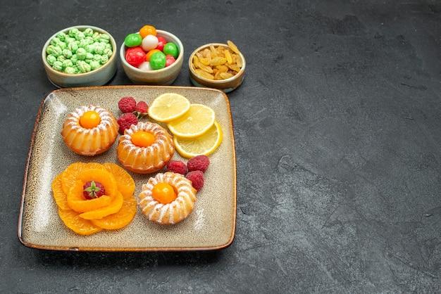 Vorderansicht köstliche kleine kuchen mit zitronenscheiben mandarinen und bonbons auf dunklem schreibtisch tee fruchtkeks süße kekskuchen