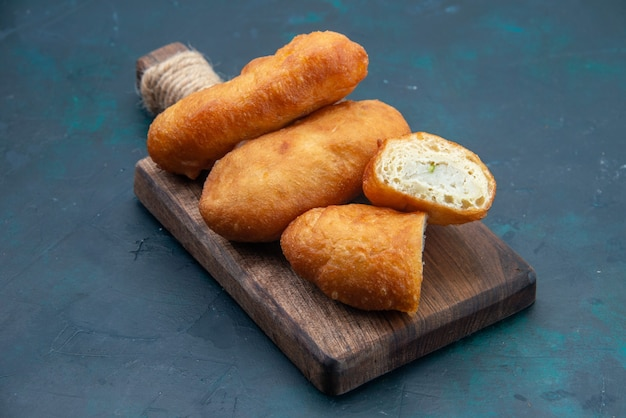 Vorderansicht köstliche kuchen mit fleischfüllung auf der dunkelblauen oberfläche teigkuchen brot brötchen essen backen gebäck