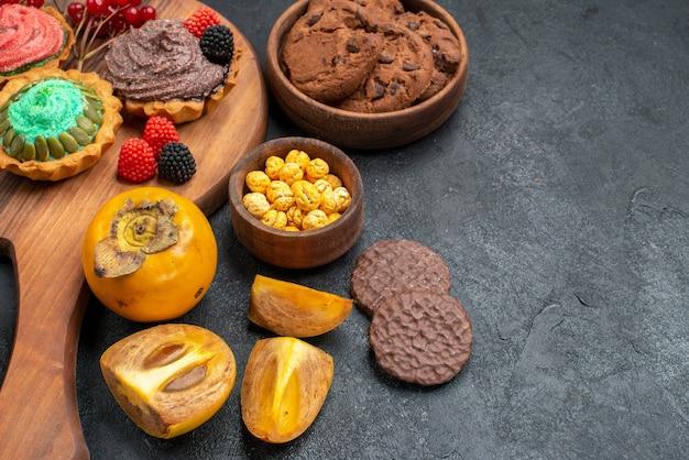 Vorderansicht köstliche kuchen mit keksen und früchten auf dunklem hintergrund