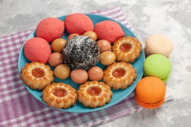 Vorderansicht köstliche kuchen mit keksen und macarons auf weißem wandkuchenkeks süßer zuckerkuchenplätzchen
