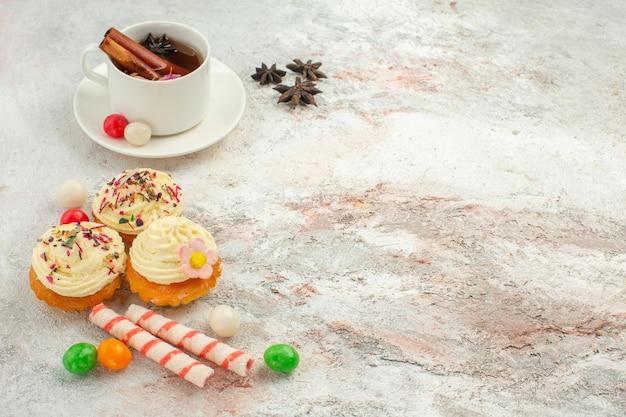 Vorderansicht köstliche kuchen mit süßigkeiten und tasse tee auf hellweißem hintergrund tee süßigkeiten keks kuchen süßes dessert