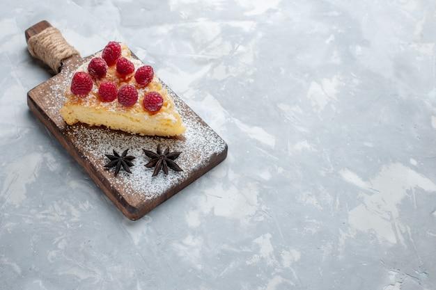 Vorderansicht köstliche kuchenscheibe mit himbeeren auf leichtem schreibtischkuchenkeks süßer zuckerauflauf