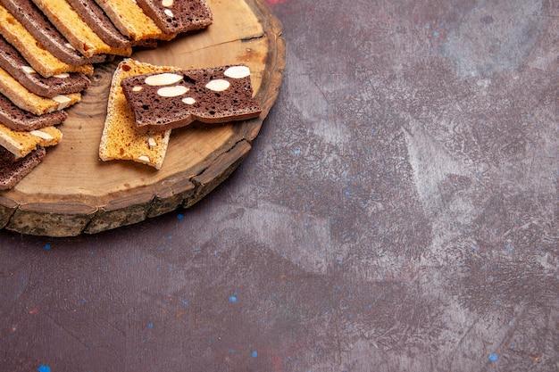 Vorderansicht köstliche kuchenscheiben mit nüssen auf dunklem raum