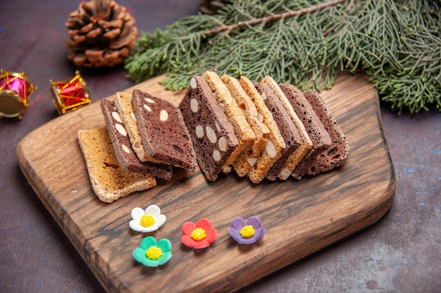 Vorderansicht köstliche kuchenscheiben mit nüssen und kakao auf dem dunklen raum
