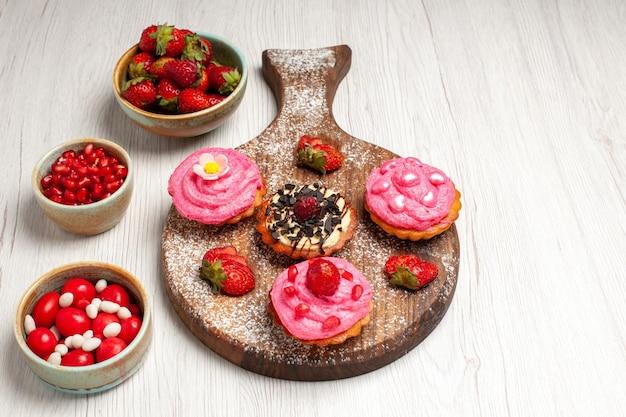 Vorderansicht köstliche obstkuchen cremige desserts mit früchten auf weißem hintergrund sahnekekse dessert süßer kuchentee