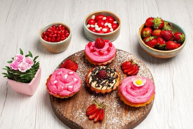 Vorderansicht köstliche obstkuchen cremige desserts mit früchten auf weißem hintergrund sahneplätzchen-dessert süßer kuchentee