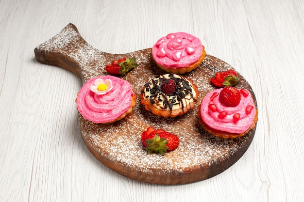 Vorderansicht köstliche obstkuchen cremige desserts mit früchten auf weißem hintergrund sahnetee dessert keks kuchen cookie