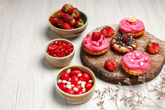 Vorderansicht köstliche obstkuchen cremige desserts mit süßigkeiten und früchten auf weißem hintergrund sahneplätzchen-dessert süßer kuchentee