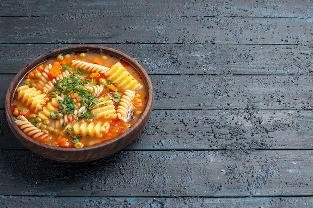 Vorderansicht köstliche pastasuppe aus spiralförmiger italienischer pasta mit grüns auf dem dunklen schreibtischgericht italienische pastasauce suppe abendessen