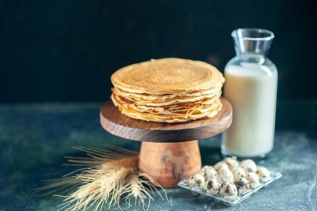 Vorderansicht köstliche pfannkuchen auf holzschreibtisch und dunkler frühstücks-dessert-kuchen-kuchen süßer milch-honig-morgen