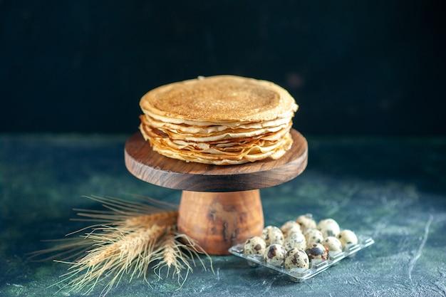 Vorderansicht köstliche pfannkuchen auf holzschreibtisch und dunkler frühstücks-dessert-kuchen-kuchen süßer milch-morgen-tee