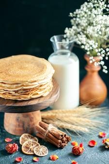 Vorderansicht köstliche pfannkuchen auf holzschreibtisch und dunkler frühstückskuchenkuchen süßer honigmorgen-tee-dessert