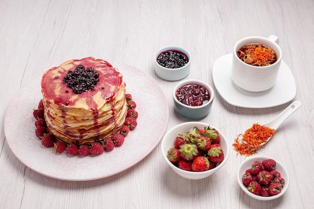 Vorderansicht köstliche pfannkuchen mit erdbeertasse tee auf weißem schreibtisch kuchen keks süße fruchtkuchen beere