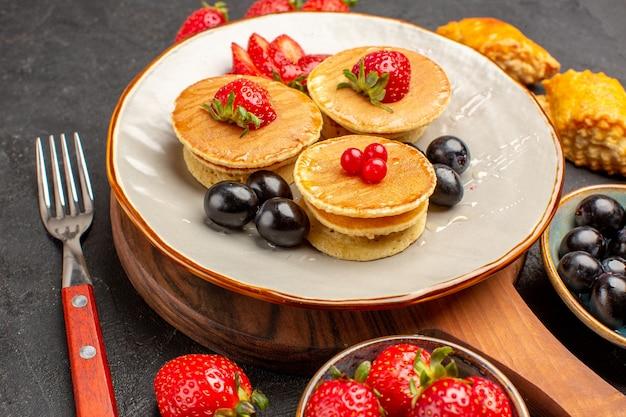 Vorderansicht köstliche pfannkuchen mit früchten auf einem dunklen kuchenfrucht süßer kuchen der dunklen oberfläche