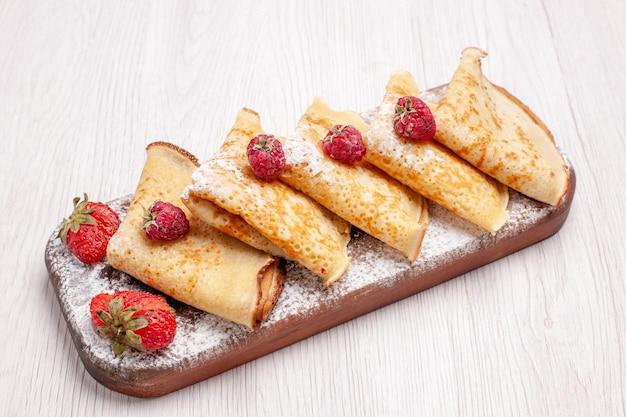 Vorderansicht köstliche pfannkuchen mit früchten auf weißem schreibtisch süße dessertfrucht pfannkuchen zucker Kostenlose Fotos