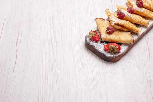 Vorderansicht köstliche pfannkuchen mit früchten auf weißem schreibtisch süße dessertfrüchte pfannkuchen zucker