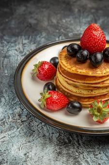 Vorderansicht köstliche pfannkuchen mit früchten und beeren auf dunklem bodenkuchenfruchtdessert