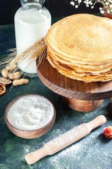 Vorderansicht köstliche pfannkuchen mit milch auf dunkelblauem dessertfrühstück honigmilch süßer morgenkuchen
