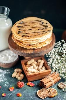 Vorderansicht köstliche pfannkuchen mit nüssen auf dunkelblauem kuchen milchdessert süßer morgenkuchen honigfrühstück