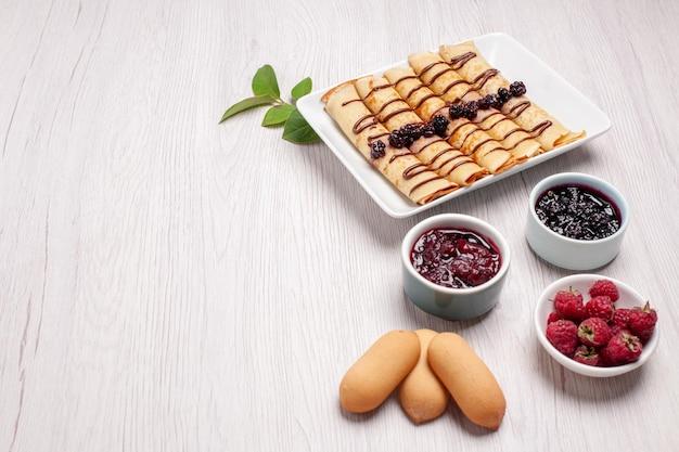 Vorderansicht köstliche pfannkuchenröllchen mit marmelade und keksen auf weißem raum