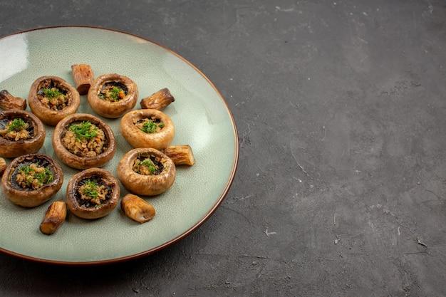 Vorderansicht köstliche pilzmahlzeit gekocht mit grüns auf dem dunklen hintergrundgericht abendessenmahlzeit kochender pilz
