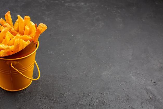 Vorderansicht köstliche pommes frites in einem kleinen korb auf dunklem raum Kostenlose Fotos