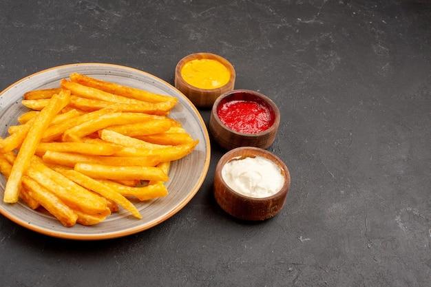 Vorderansicht köstliche pommes frites mit gewürzen auf dunklem raum