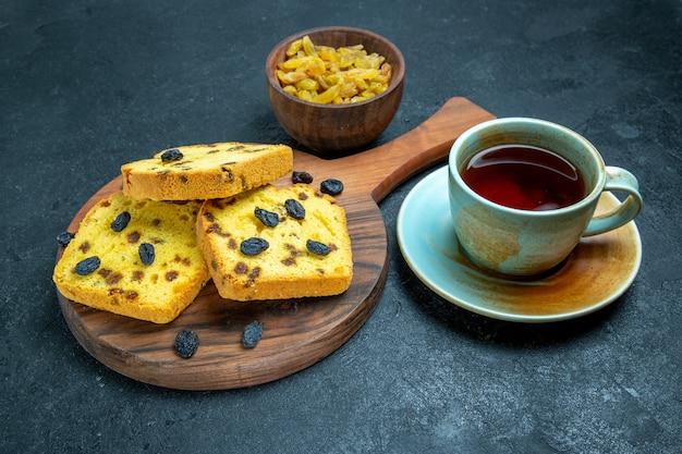 Vorderansicht köstliche rosinenkuchen mit frischen rosinen und einer tasse tee auf dunklem raum